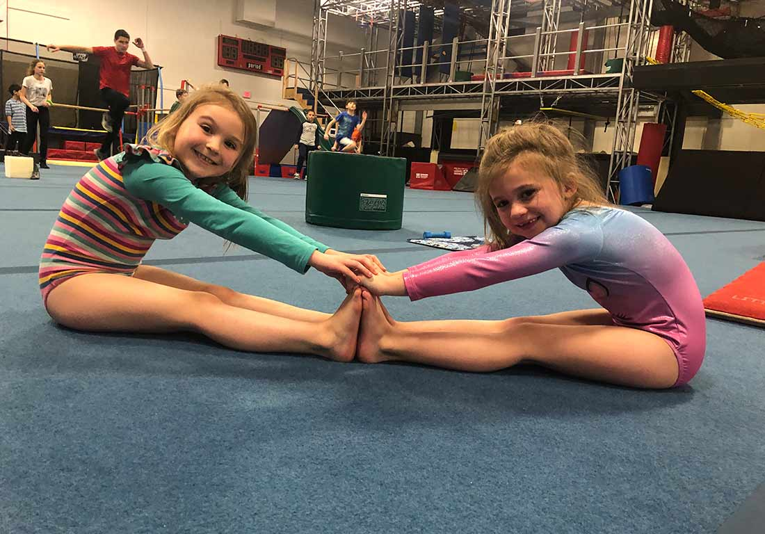 young gymnasts touching hands and toes