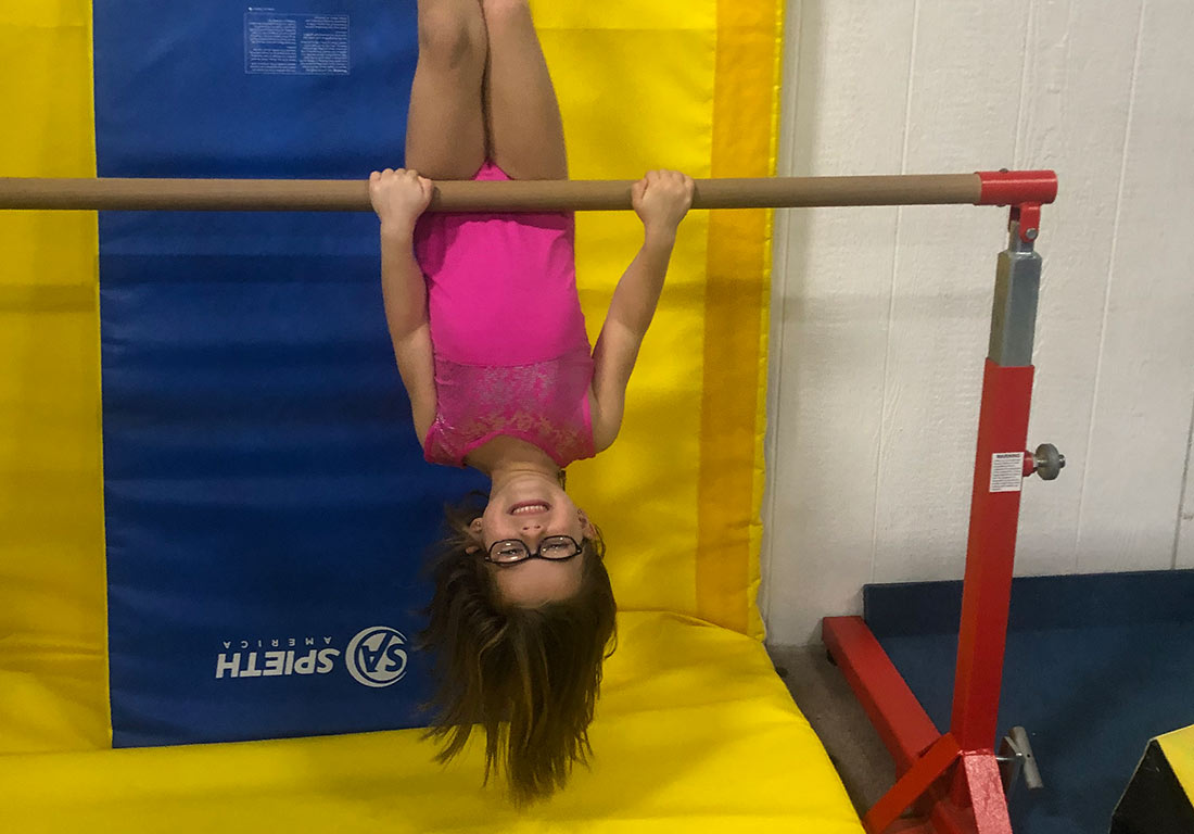 young gymnast hanging upside down
