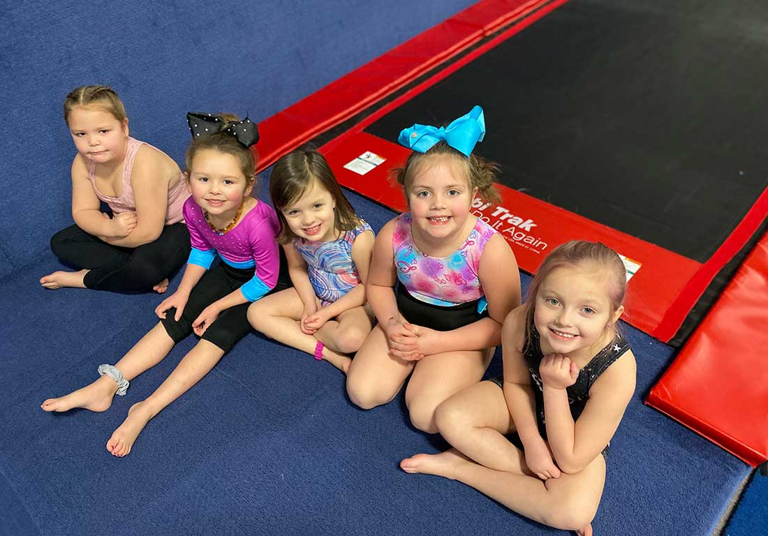young gymnasts sitting in front of the tumble track
