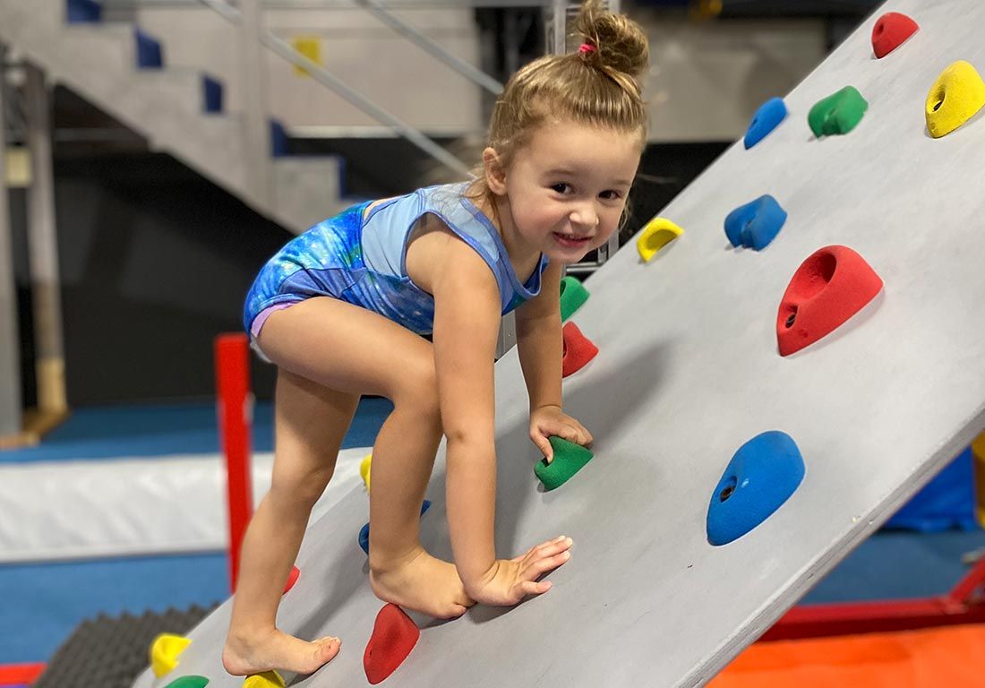 young gymnast climbing and smiling on rock wall